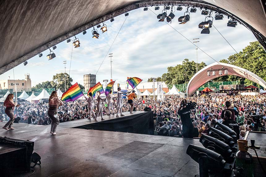 Framför ett packat publikhav står underhållare på Prides stora scen. Det är en varm sommardag.